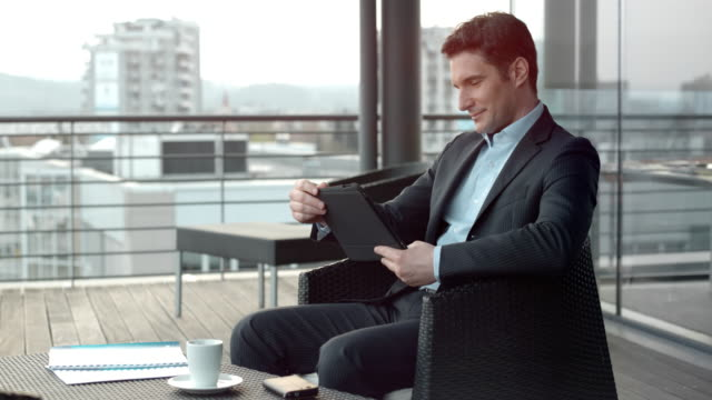 Caucasian man scrolling his digital tablet while sitting in a rooftop terrace lounge in the city