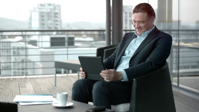 Caucasian man smiling while using his digital tablet in a terrace lounge in the city