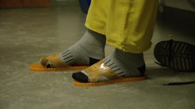 a caucasian man takes off his right black-laced shoe and puts his socked foot into an orange, plastic sandal - sock stock videos & royalty-free footage