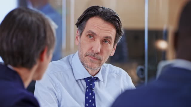 caucasian man talking with his colleagues in a meeting - film moving image stock videos & royalty-free footage