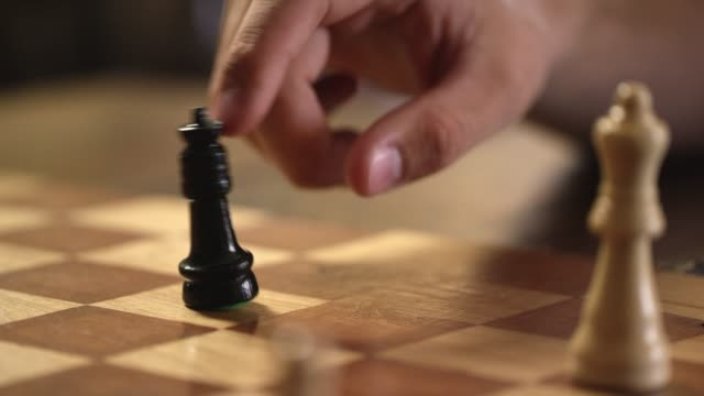 vidéos et rushes de un homme de race blanche se renverse la reine de son adversaire dans un jeu d'échecs - se déplacer vers le bas