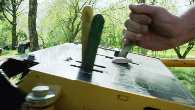 a caucasian man uses a levers on a control panel to operate machinery outdoors in an uncultivated area with trees on a sunny day - lever stock videos & royalty-free footage