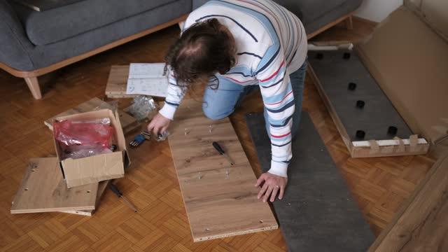 コーカサスの男は、一緒にクローゼットを置くために作業ツールを使用して - 中年の男性一人点の映像素材/bロール