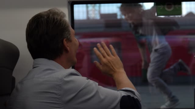 vidéos et rushes de homme caucasien agitant au revoir à ses fils qui courent en dehors de sa fenêtre du train - séparation