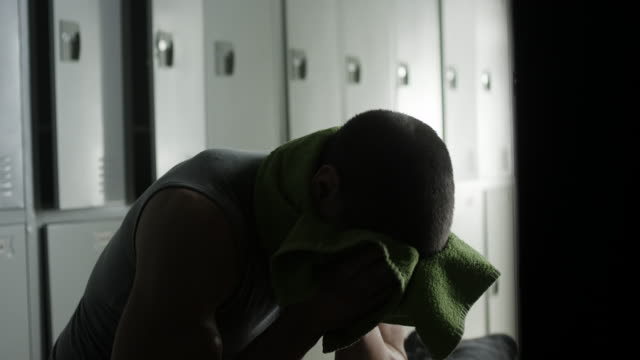 Caucasian man wiping sweat from forehead in locker room