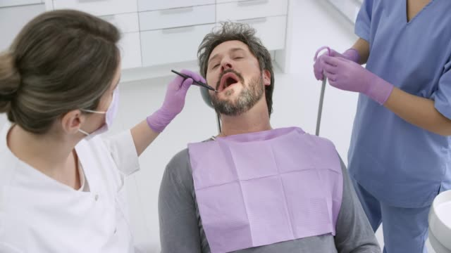 caucasian man with a beard getting his teeth repaired by a female dentist - protective glove stock videos & royalty-free footage