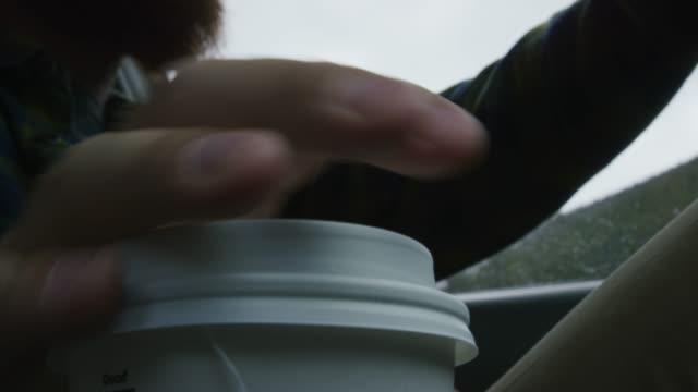 あごひげを持った白人の男が行きカップを拾い、熱い飲み物を一口飲んで、冬に山の中を走りながらコンソールに戻します - 落ち着かない点の映像素材/bロール