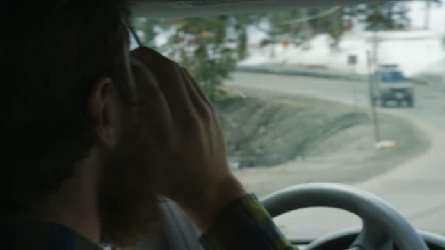 vídeos de stock, filmes e b-roll de um homem caucasiano com uma barba toma uma bebida fora de his a-vai o copo enquanto conduz através das montanhas rochosas de colorado no inverno - coffee drink