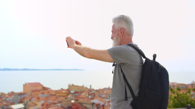 Caucasian man with grey hair and beard holding a smartphone and taking photos on a path above the picturesque coastal town
