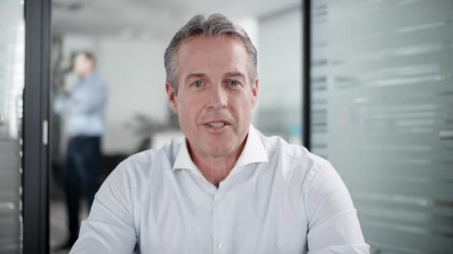 Kaukasischen Mann mit grauem Haar mit einer Videokonferenz aus seinem Büro