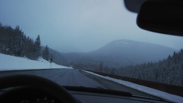 a caucasian man with his hand on the steering wheel drives on interstate 70 in the rocky mountains of colorado in under a darkening, overcast sky in winter - headlight stock videos & royalty-free footage
