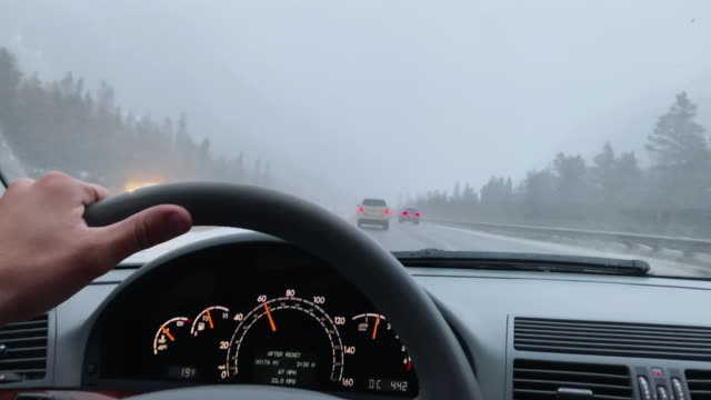 a caucasian man with his hand on the steering wheel drives on interstate 70 in the rocky mountains of colorado in under an overcast sky in winter - steering wheel stock videos & royalty-free footage