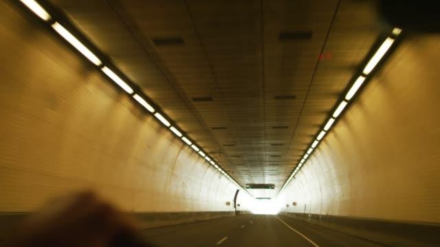 vidéos et rushes de un homme caucasien avec sa main sur le volant conduit à travers un tunnel et se termine dans une lumière vive - intérieur de véhicule