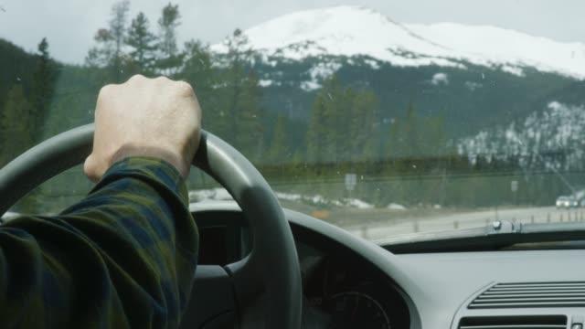 ステアリングホイールの上に手を持った白人の男は、冬にコロラドのロッキー山脈での州70間の過去の建設に西行きを駆動します - 職業 運転手点の映像素材/bロール