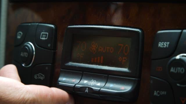 白人男性の指が車両のダッシュボードの温度コントロールボタンを押し、ドライバーの熱を上げる - 電源点の映像素材/bロール