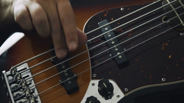 a caucasian man's fingers pluck the strings and press down on the fretboard of a five-string electric bass guitar while playing music - fretboard stock videos & royalty-free footage