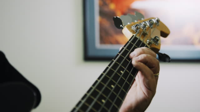 a caucasian man's fingers press down on the fretboard of a five-string electric bass guitar while playing music indoors - fretboard stock videos & royalty-free footage