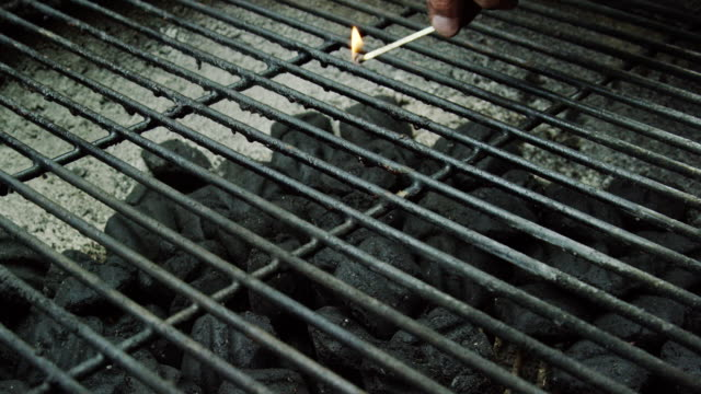 a caucasian man's hand drops a lit wooden match into a an outdoor barbecue grill, lighting the charcoal briquettes on fire in preparation for grilling - coal stock videos & royalty-free footage