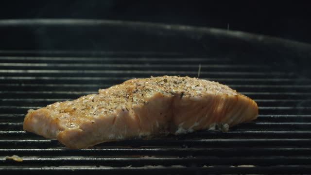 a caucasian man's hand sprinkles seasoning on to a salmon steak over a flaming barbecue grill - grilled stock videos and b-roll footage