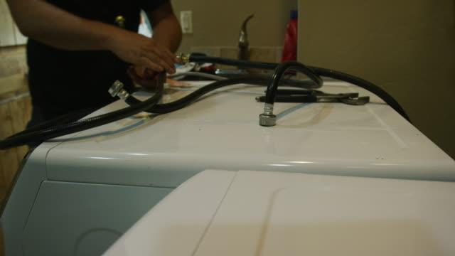 stockvideo's en b-roll-footage met de handen van een blanke man verzamelen de afvoerpijp en water slangen en plaatsen ze bovenop een wasautomaat ter voorbereiding op het verplaatsen - wasmachine