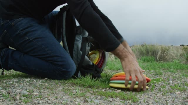 A Caucasian Man's Hands Pick Up Disc Golf Discs off the Ground and Places Them Into a Disc Golf Bag