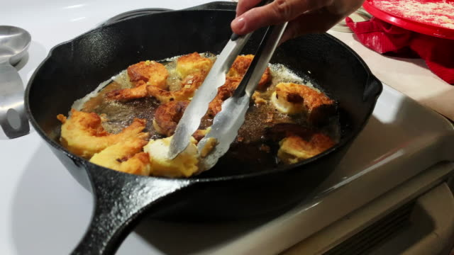 a caucasian man's hands turn over breaded shrimp while frying them in a cast iron skillet in a kitchen - breaded stock videos and b-roll footage
