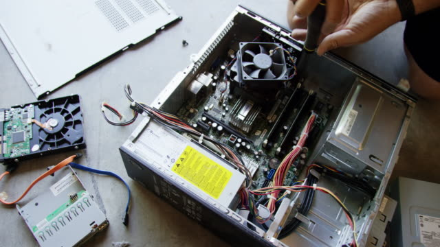 a caucasian man's hands use a screwdriver to dismantle a computer lying in pieces of the floor - electrical equipment video stock e b–roll