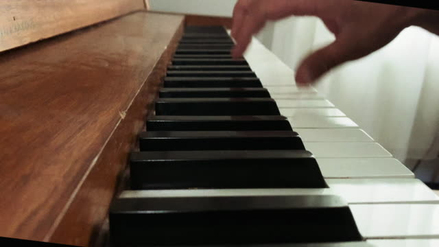 vídeos de stock e filmes b-roll de a caucasian man's right hand plays a piano's keys indoors - pianista