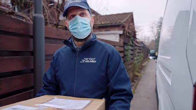 vidéos et rushes de chauffeur caucasien de livraison masculin de gig de mi-adulte avec le paquet facial de fixation de masque et le livrant au client - un seul homme d'âge moyen