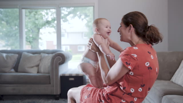 a caucasian mother and her 6 month old baby boy bonding on t family couch in the living room shot in slow motion - 6 11 månader bildbanksvideor och videomaterial från bakom kulisserna