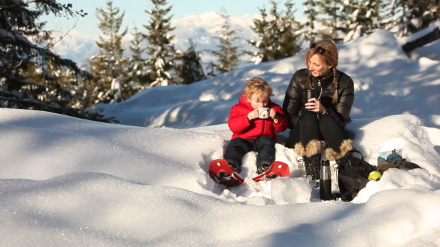 Caucasian mother and son drinking cocoa in snow