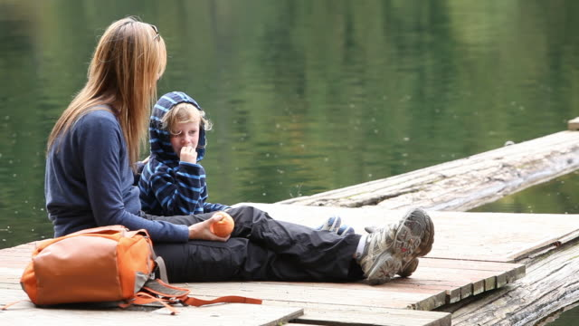 Caucasian mother and son eating snack on dock at lake