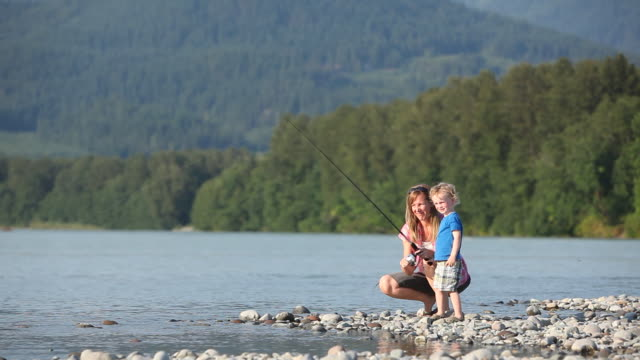 Caucasian mother and son fishing in river