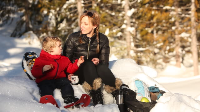 Caucasian mother and son having picnic in snow