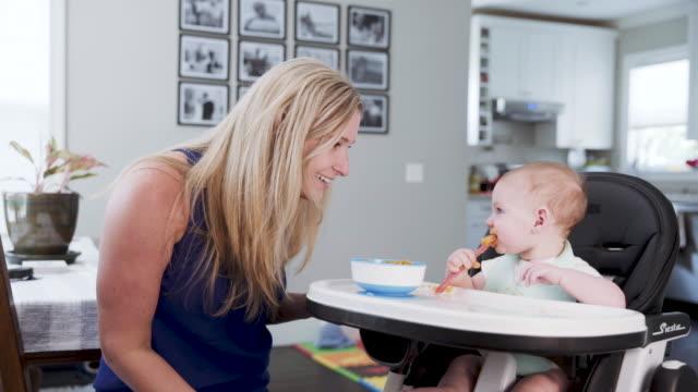 a caucasian mother feeding her 6 month old baby boy in a high chair - 6 11 månader bildbanksvideor och videomaterial från bakom kulisserna