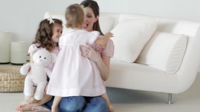Caucasian mother hugging her daughters