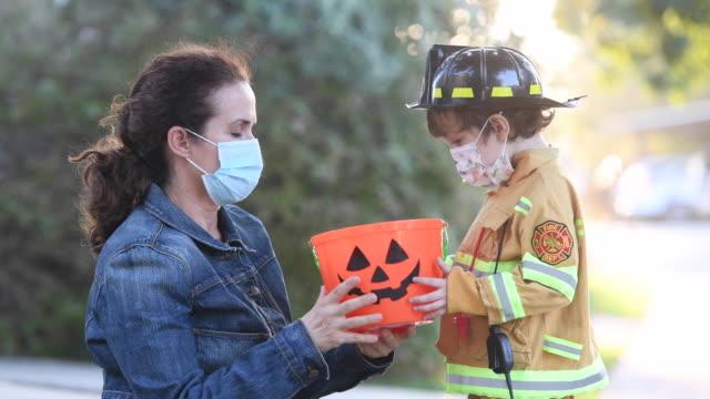白人の母親は、トリックを尋ねるか、ハロウィーンを扱うために行く前に、彼女の息子に保護フェイスマスクを入れました - 菓子類点の映像素材/bロール