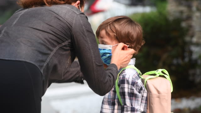 caucasian mother putting on a protective face mask on her son and then walking him to school - state of emergency stock videos & royalty-free footage