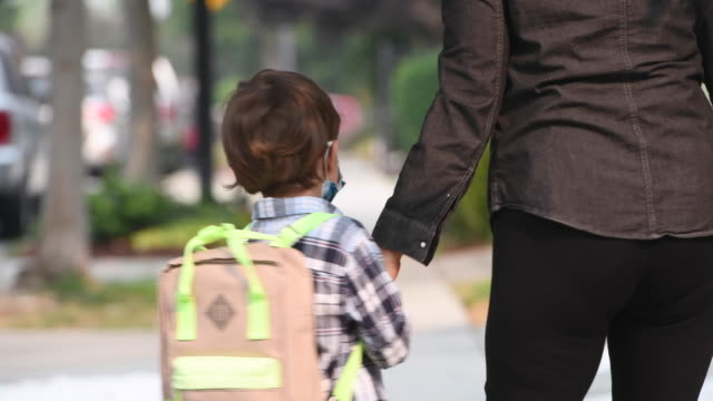caucasian mother putting on a protective face mask on her son and then walking him to school - backpack stock videos & royalty-free footage
