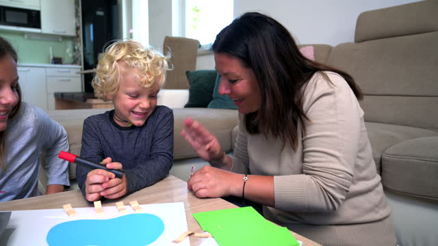 caucasian mother, son and daughter making and playing with paper model at home - family with two children stock videos & royalty-free footage