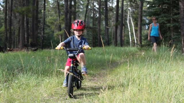 vidéos et rushes de caucasian mother teaching son to ride bicycle - vue de face