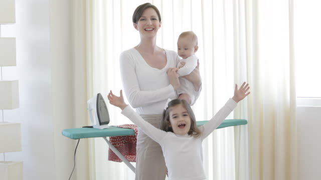 vídeos y material grabado en eventos de stock de caucasian mother with baby and little girl at ironing board - tabla de planchar