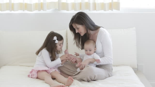 Caucasian mother with baby and little girl sitting on bed