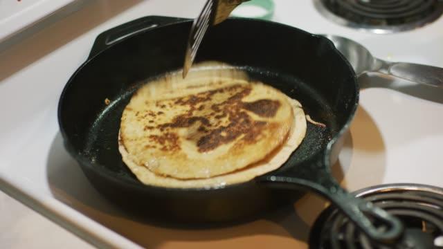 vídeos y material grabado en eventos de stock de una persona caucásica usa un turner de panqueque de metal para entregar una quesadilla de cocina (tortillas y queso) cocinando en una sartén de hierro fundido en un quemador de rango - sartén plana