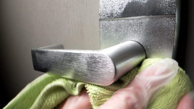 caucasian person's glove hand spraying and cleaning a metal doorknob in a public commercial office building with alcohol-based disinfectant to prevent the spread of covid sars ncov 19 coronavirus swine flu h7n9 influenza illness during cold and flu season - caretaker stock videos & royalty-free footage