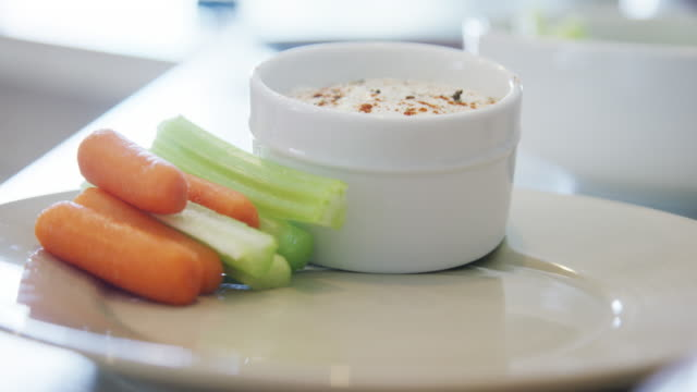 a caucasian person's hand stacks carrot and celery sticks neatly on a plate next to a small bowl of ranch dipping sauce - dipping stock videos & royalty-free footage