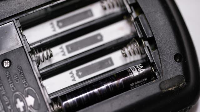 vídeos de stock, filmes e b-roll de as mãos de uma pessoa caucasiano instalam baterias do triplo a (aaa) em um dispositivo eletrônico - pilha arranjo