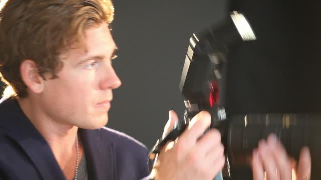 vidéos et rushes de caucasian photographer taking pictures in studio - seulement des jeunes hommes