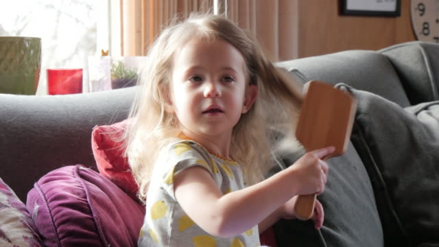 Caucasian preschooler brushing her hair on sofa