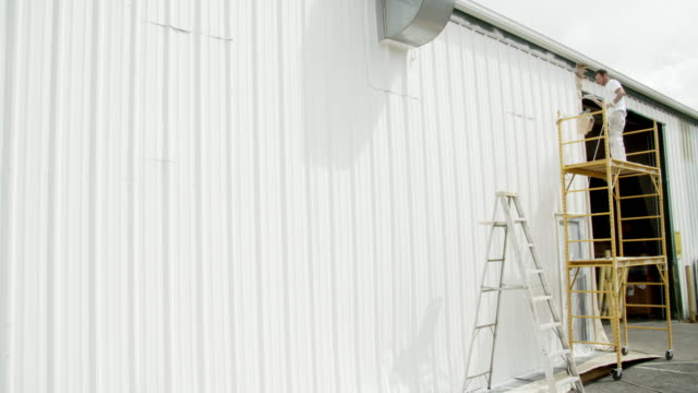 a caucasian professional painter in his thirties uses a paint sprayer to paint the outside of a metal warehouse while standing on a scaffold under partly cloudy sky - ladder stock videos & royalty-free footage